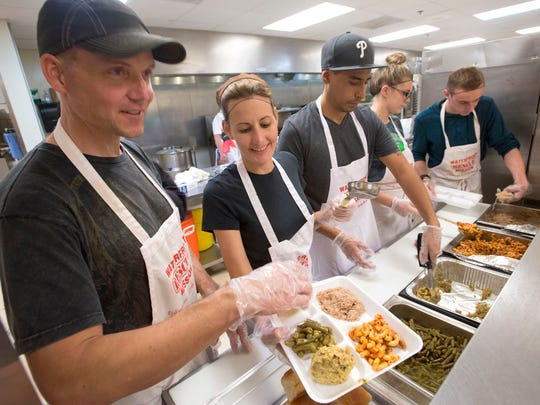 Volunteers, left to right, Ted Oglesbee, Tanya Manning, Brady Noltie,  Jewel LaCross, and Chase Manning, come together to serve the less fortunate a holiday meal at the Waterfront Mission in Pensacola Thursday evening.