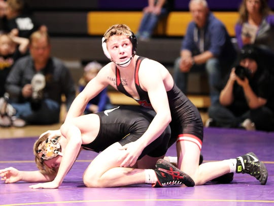 Fort Dodge senior Brody Teske, who is an undefeated three-time state champion and Penn State recruit, checks the clock as he records another victory in his 126-pound match with Johnston sophomore James Edwards as the Fort Dodge Dodgers grapple with the Johnston Dragons in a top-10 wrestling dual at Johnston High School.