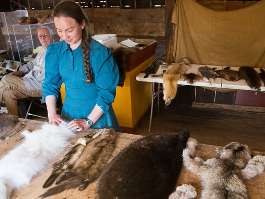 A visitor feels the pelt of an artic fox at the Frontier