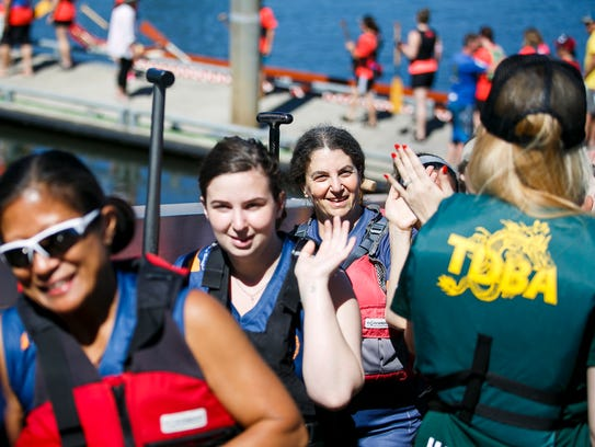 Dragon boat teams high five in between races at the