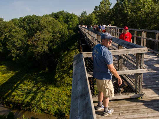 Walkers cross the old trestle bridge Monday, Sept. 5, 2016, during the annual Trestle Trek along the Wadhams-to-Avoca Trail.
