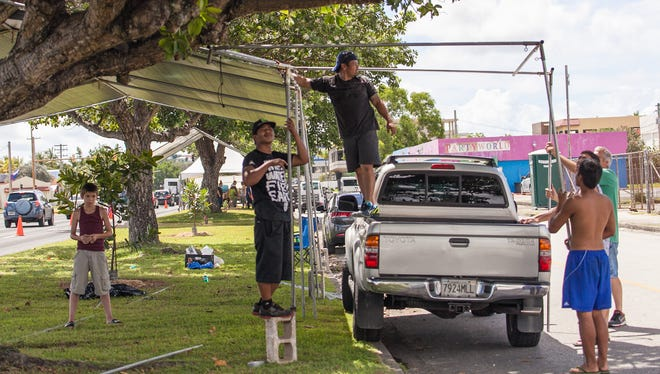 Residents set up their canopies along Marine Corps Drive between the Hagåtña Boat Basin area and Anigua on July 20, 2013, in preparation for the 69th Liberation Day parade.