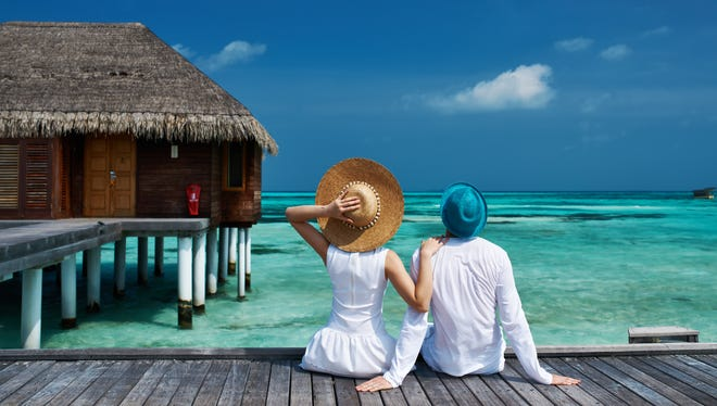 Couple on a tropical beach jetty at Maldives