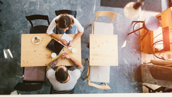 Overhead view of two business people sitting in cafe