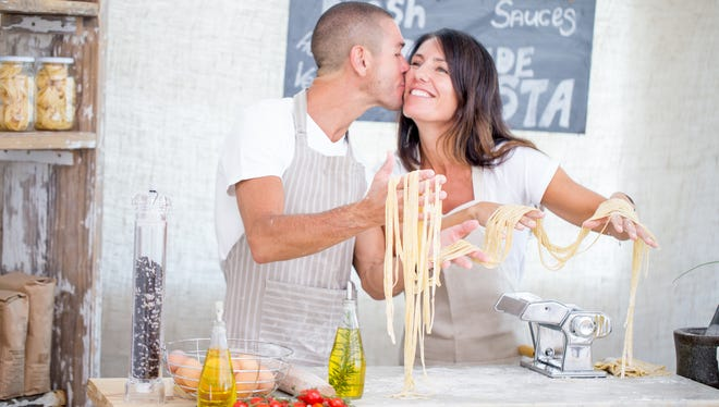 Young couple attending a cooking class where they learn how to make homemade pasta. Staring with preparing the pasta dough and learning how to use the pasta machine later. Series of images covering the whole procedure.