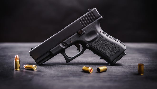 Pictured is a black 9mm pistol on a black wooden table.