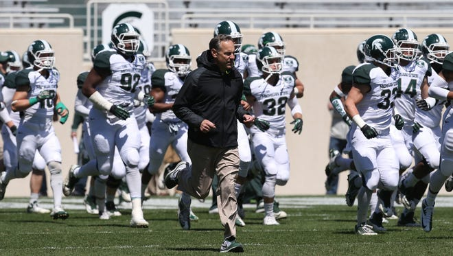 Coach Mark Dantonio leads his team onto the field during last year's Michigan State spring game on April 26, 2014. This year's game is Saturday at 2 p.m. at Spartan Stadium.