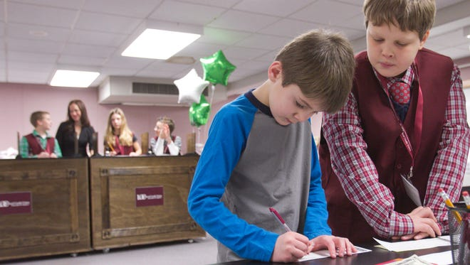 6-year-old Northwest Elementary kindergartener Preston Dickey is helped with a deposit by fifth grader Gus Berntsen, who serves as the branch manager of the newly opened LOC Federal Credit Union branch at the Howell area elementary school on Friday, Feb. 3, 2017.