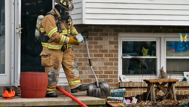 A firefighter brings out a wrapped Christmas present to add to a pile of other gifts outside a house that caught fire Friday in Jackson Township.