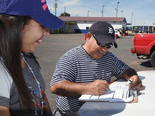 Pamela Miramontes (left), volunteer, works the Loncheria El Parian food truck and registers Francisco Sanchez, of Lincoln Park, along Dix Avenue.