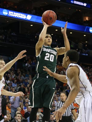 Michigan State's Travis Trice scores against the Virginia Cavaliers' Malcolm Brogdon during second half action on Sunday, March 22,2015 at the Time Warner Cable Arena.