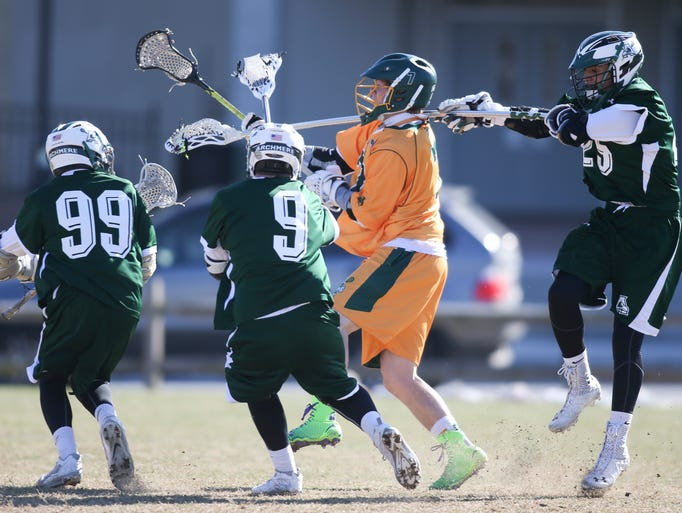 St. Mark's Rhett Schweizer is swarmed by Archmere's (from left) Christian Conaty, Sean Devine and Nick Salameda in the first half of Archmere's 10-6 win at St. Mark's High School, Wednesday, March 26, 2014.