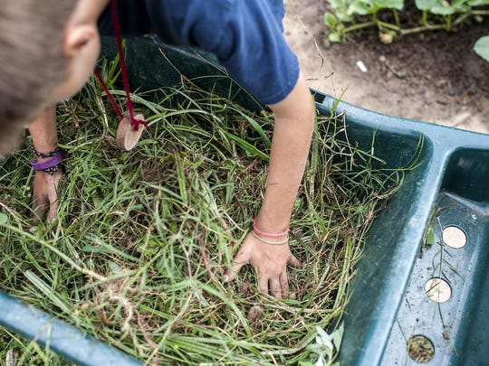 Mason Vaughn, 12, moves weeds to a compost bin in the garden at Haywood Street Congregation in Asheville. Mason is part of Carolina Cross Connection, a nonprofit ministry that brings people from all over to do urban outreach in Asheville.