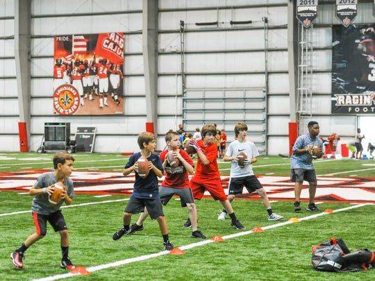 Quarterbacks line up to throw at a Cajuns youth football camp last week.