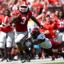 Sep 20, 2014; Athens, GA, USA; Georgia Bulldogs running back Todd Gurley (3) runs down the sideline against Troy Trojans defensive back Montres Kitchens (1) during the first quarter at Sanford Stadium. Mandatory Credit: Dale Zanine-USA TODAY Sports