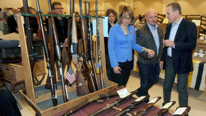Former U.S. Rep. Gabrielle Giffords, D-Ariz. (left to right), her husband, Mark Kelly, and New York Attorney General Eric Schneiderman tour a gun show in 2013.