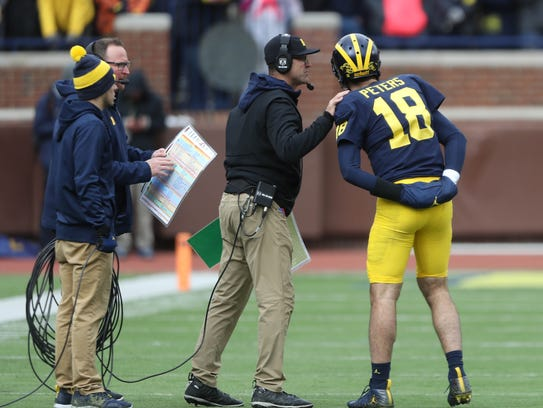 Jim Harbaugh talks with Brandon Peters in the fourth