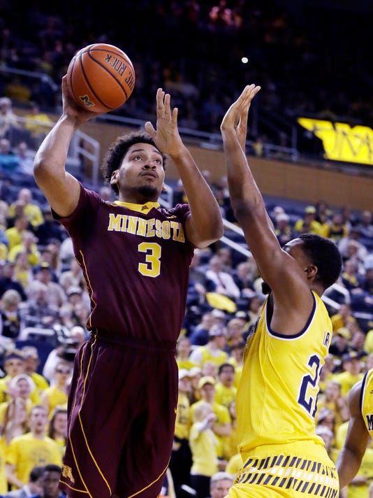 Minnesota forward Jordan Murphy (3) shoots over the defense of Michigan guard Zak Irvin (21) during the first half of an NCAA college basketball game, Wednesday, Jan. 20, 2016 in Ann Arbor, Mich. (AP Photo/Carlos Osorio)