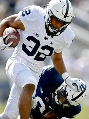 Penn State running back Journey Brown, top, runs downfield with the ball during the school's Blue-White spring college football game on Saturday, April 21, 2018, in State College, Pa.