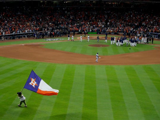 The Houston Astros celebrates after Alex Bregman's game winning single during Game 5 of baseball's World Series against the Los Angeles Dodgers Monday, Oct. 30, 2017, in Houston. The Astros won 13-12 to take a 3-2 lead in the series. (AP Photo/Charlie Riedel)
