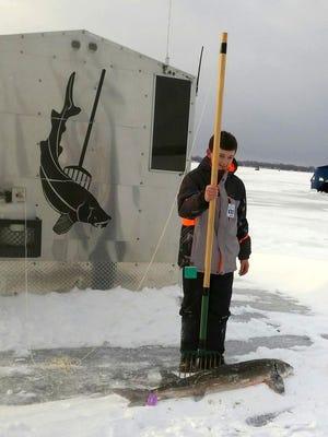 Cole Hudson with a harvested sturgeon on Feb. 4, 2017 on Black Lake.