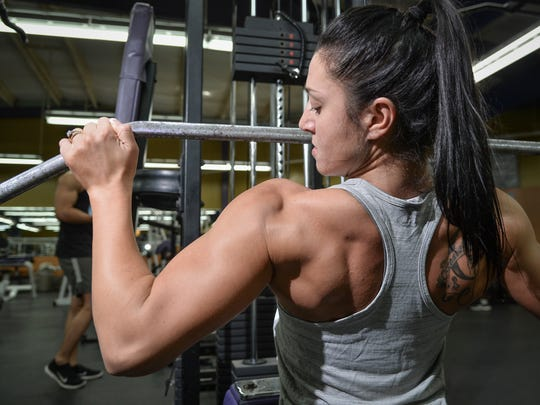 Sarah Pavlik, 2016 Michelob Ultra National Body Fitness champion, watches her muscle engagement during lat pull-downs at Paradise Fitness Center in Hagåtña on Nov. 17, 2016.