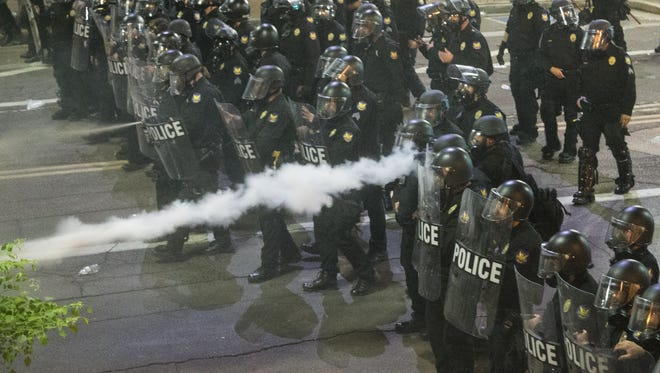 Phoenix police use gas on protesters of President Donald Trump outside the Phoenix Convention Center in Phoenix on Aug. 22, 2017.