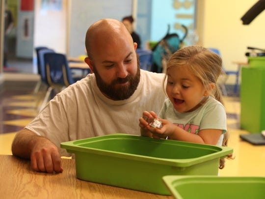 Paul McCandless of Norwood, Pennsylvania, watches his 3-year-old daughter Ava react to finding a cube in a bin of beans and other objects Sunday at the Delaware Children's Museum in Wilmington.