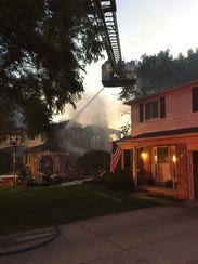 Firefighters battle a house fire that destroyed a two-story
