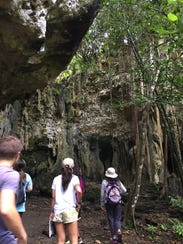 A tour group walks through the caves of Ritidian on
