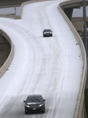 Drivers make their way on a sleet-covered highway, Monday, Feb. 23, 2015, in Dallas. Freezing rain affected travel in nearly half of Texas on Monday, and winter storm warnings were issued in the northern part of the state. (AP Photo/LM Otero)