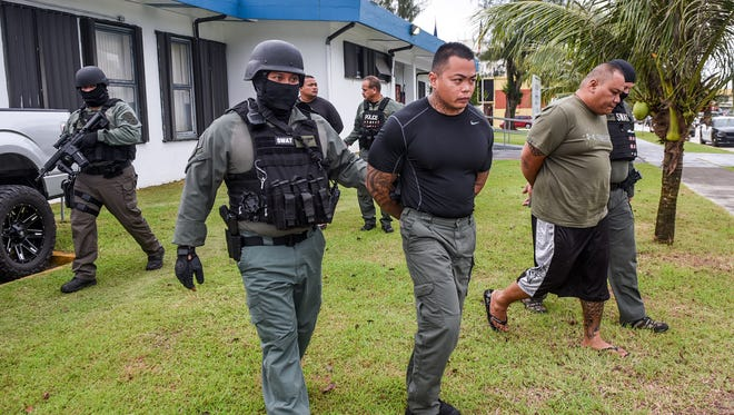 Department of Corrections Officers Franklin Rosalin, center, and Gerry Hocog are escorted away from the Guam Police Department's HagΌtЖa precinct on Thursday, Aug. 24, 2017.