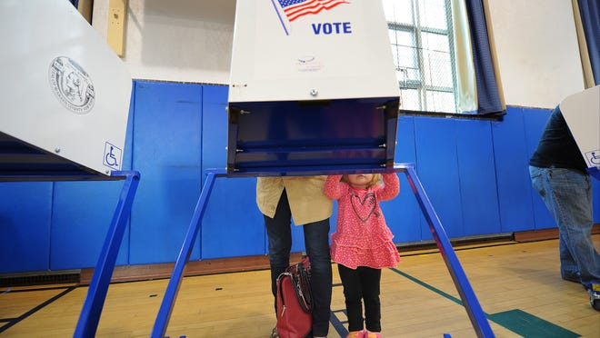Cassidy Dezik, 2, stands at the voting booth while her mother, Katie Dezik, casts her vote on Election Day in the Sanford Street School in Glens Falls, N.Y., Tuesday, Nov. 4, 2014. (AP Photo/The Post-Star, Steve Jacobs) ORG XMIT: NYGLE101