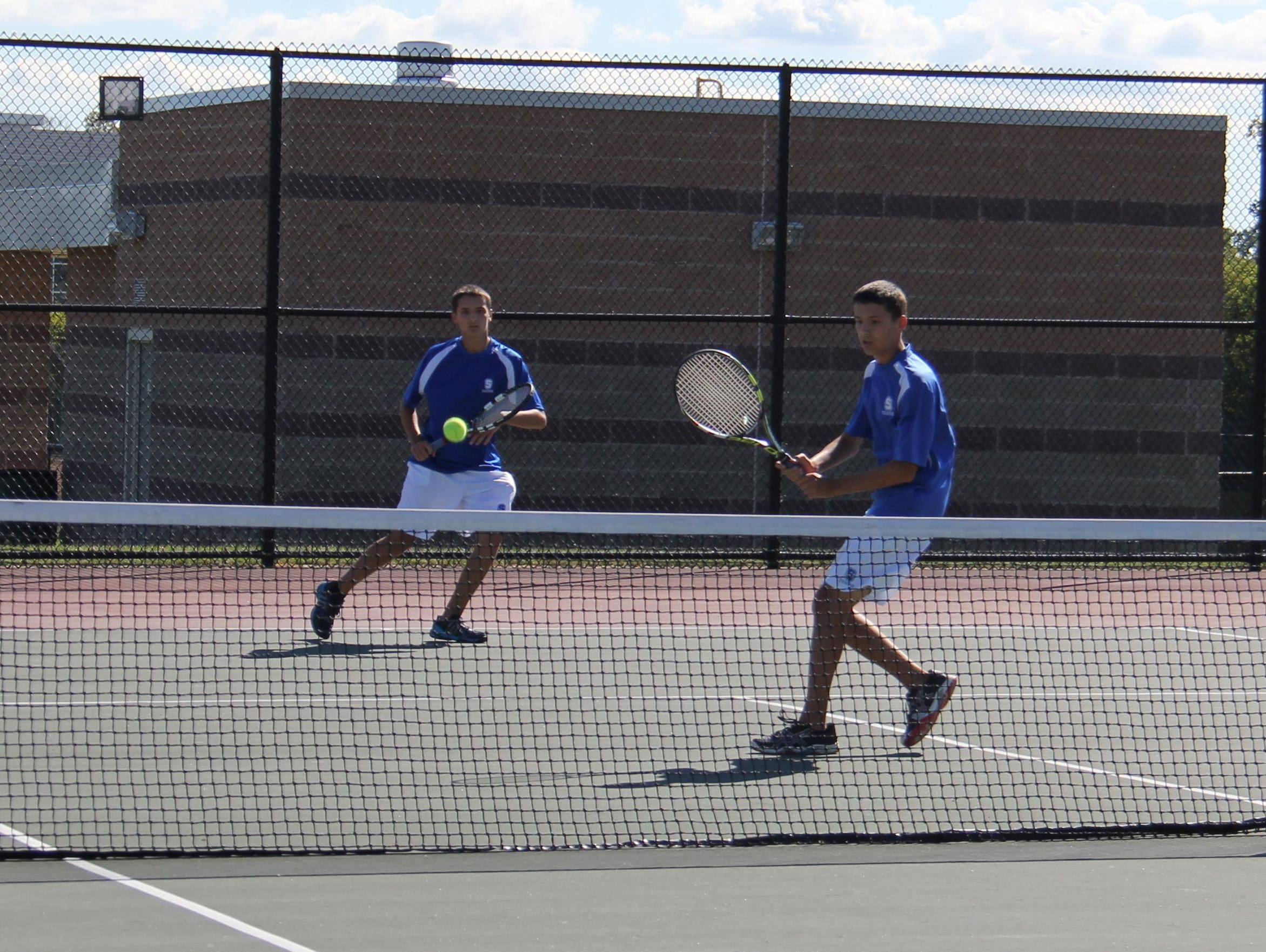 Conor Sweet (foreground) gets ready to smack the ball while doubles teammate and twin brother Caden Sweet watches.