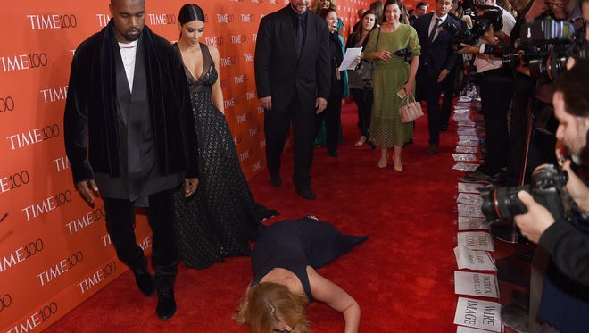 Honoree and comedian Amy Schumer pretends to trip and fall on the floor in front of honorees Kim Kardashian and Kanye West as they attend the Time 100 Gala celebrating the Time 100 issue of the Most Influential People at The World at Jazz at Lincoln Center on April 21, 2015 in New York.