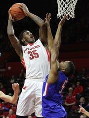 Rutgers' Greg Lewis shoots around UMass Lowell's Dontavious