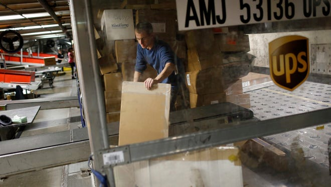 """FILE - In this Nov. 20, 2015, file photo, UPS employee Justin Sims prepares to place a package on a conveyor belt while unloading a container at Worldport in Louisville, Ky. UPS says it will deliver a record 1.3 million returns to retailers on Jan. 5, dubbed """"National Returns Day"""" and about 5 million during the first week of 2017. (AP Photo/Patrick Semansky, File)"""