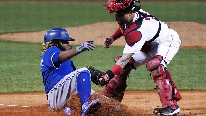 Boston's Christian Vazquez tags out Toronto's Vlad Guerrero Jr. after Guerrero tried to score on a fielding error by Michael Chavis in the fourth inning Thursday night.