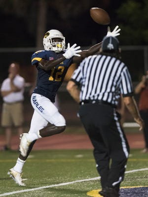Naples wide receiver Wooby Theork pulls in a touchdown pass in front of an official during the game against Golden Gate at Naples High Friday night, September 30, 2016.