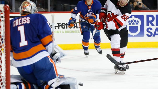 Islanders goalie Thomas Greiss (1) blocks a shot by Devils center Kevin Rooney (58) during the third period of a preseason game in 2017. (AP Photo/Kathy Willens)