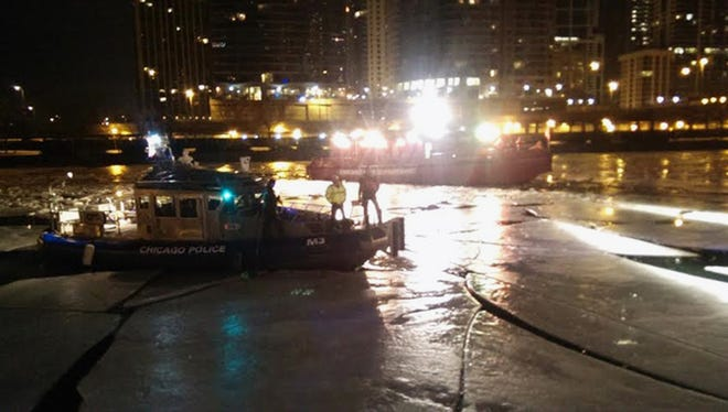 Chicago Police and Fire Department boats are seen on the Chicago River in downtown Chicago on Jan. 13, 2014, where a 26-year-old man was pulled from the water after he jumped over a fence to get a cellphone he'd dropped into the water.