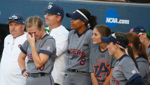 Auburn's Anna Gibbs, left, wipes her eyes as she and