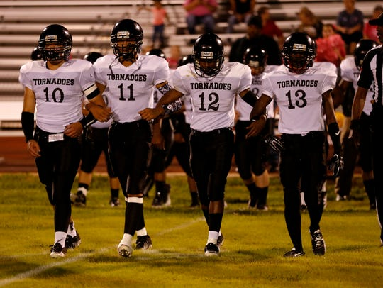 Gainesville State School players walk to midfield for