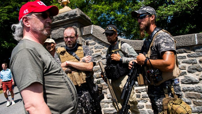 A group of individuals, some armed, talk near an entrance to the Gettysburg National Cemetery in Gettysburg National Military Park on Saturday, July 4, 2020.