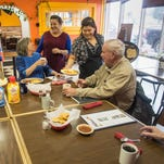 Yeni Mora visits with some of her regulars, while Maria Cervantes serves them in Dillon at Mora's restaurant, Los Koritas.