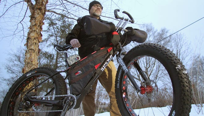 Donald Wood shows the fat tire bike he'll use in an upcoming Arrowhead 135 Endurance race in International Falls, Minn. Though the specialty bike is sturdily built, its carbon fiber frame keeps its total weight below 50 pounds.