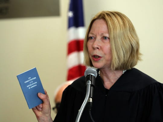 The Hon. Linda Christopher, Associate Justice of the Appellate Division-Supreme Court, holds a pocket version of the Unites States Constitution, as she speaks during a Yom HaShoah, Holocaust Memorial Day ceremony at the Rockland County Courthouse April 11, 2018. The pocket constitutions were handed out to all those who attended the ceremony.
