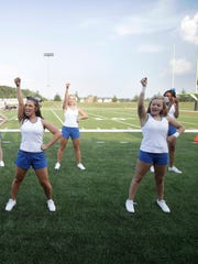 Holly Becker, middle, and members of the Hocking College football cheerleading squad cheer during the schools first football game, Monday, Aug. 31, 2015, against Ohio Northern in Ada, Ohio. With falling enrollment and a financial crisis that led to three dozen layoffs earlier this year, Hocking College officials came up with an unexpected strategy for raising the profile and attracting more students: they started a football team.