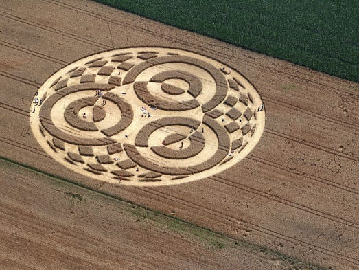 People walk through crop circles shaped into a cornfield near Raisting, southern Germany, on July 28, 2014. According to media reports, a balloonist had discovered the circle some days ago. Since then, hundreds of people came to the field to watch it, however it is unclear who did create the pattern.      AFP PHOTO / DPA / KARL-JOSEF HILDENBRAND / GERMANY OUT        (Photo credit should read KARL-JOSEF HILDENBRAND/AFP/Getty Images)