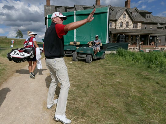 Steve Stricker waves to an acquaintance after finishing